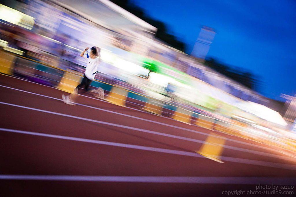 Ảnh chụp lia một vận động viên chạy thi trên đường đua.
